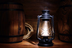 Old Kerosene Lantern Light in a Vintage Warehouse. Old kerosene lantern burning with bright flame between wood barrels in a vintage country barn warehouse Royalty Free Stock Photography
