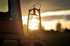 The old kerosene lantern on a tractor at sunset royalty free stock image