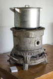 Old kerosene stove with a saucepan stands on the table beside ma Royalty Free Stock Photography