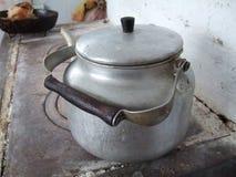 Old kettle. Old aluminium kettle on old oven Stock Image