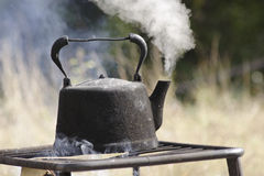 Old kettle boiling outdoors. Old metal kettle boiling outdoors over campfire Royalty Free Stock Image