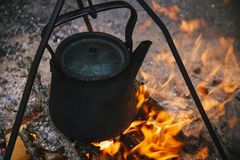 Old kettle is burning at the stake, tourists boil water on the fire. Fire campfire and cooking in the campaign Royalty Free Stock Photos