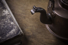 Old kettle on a grunge wooden surface Stock Photo
