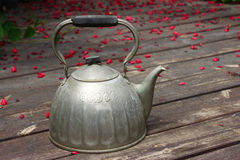 Old kettle over wooden planks. Stock Photos