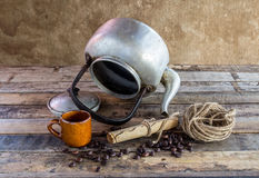 Old kettle,paper roll,rope reel and coffee beans on wooden backg Stock Photos