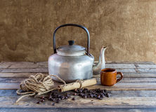 Old kettle,paper roll,rope reel and coffee beans on wooden backg Royalty Free Stock Photos
