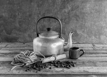 Old kettle,paper roll,rope reel and coffee beans on wooden Royalty Free Stock Image