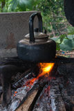 Old kettle sitting on hot fire Stock Photo