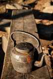 Old kettle in wooden bench outdoors Stock Image