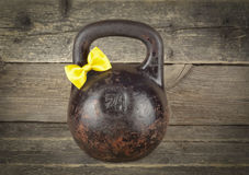 Old kettlebell with a yellow tie bow on a wooden background Royalty Free Stock Images