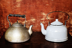 Old kettles. Two old kettles on wooden background Royalty Free Stock Images