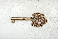 Old Key. A golden decorative vintage key on white scratched painted wood texture Royalty Free Stock Photos