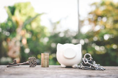 Old key coin piggy bank on wood Stock Image