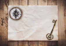Old key and Compass on Old paper vintage on wood background with space.  stock photography