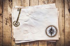 Old key and Compass on Old paper vintage on wood background with space.  royalty free stock photography