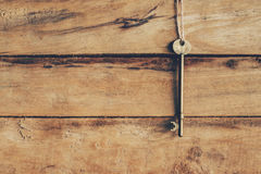 Old key hanging on wood background texture Royalty Free Stock Photos