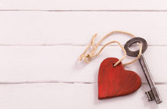 Old key with a heart on white wood stock photography