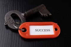 An old key with an inscription on a black table. Accessories and symbol referring to the word in the description of the key stock photo