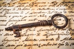 Old key on letter. Old rusty key on letter background Royalty Free Stock Images