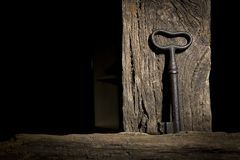 Old key on a log. Vintage key hanging on an old log royalty free stock photography