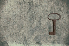 Old key on the old textured paper with natural patterns Royalty Free Stock Photography