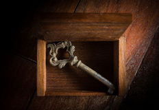 Old key in open wooden chest. Royalty Free Stock Images