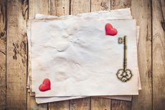 Old key and red heart on Old paper vintage on wood background with space.  royalty free stock photo