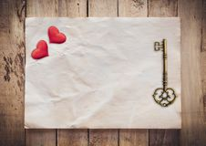 Old key and red heart on Old paper vintage on wood background with space.  stock photos