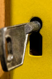 Old key is sitting in the door eye. Royalty Free Stock Photo