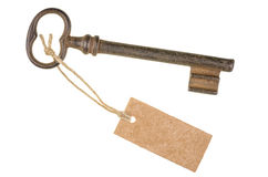Old key with a tag. On a white background Stock Photography