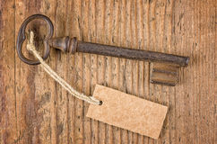 Old key with tag on a wooden board Royalty Free Stock Photos