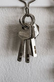 Old key vintage hanging on cement wall. Background stock image