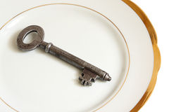 Old key on white china ware Royalty Free Stock Photo