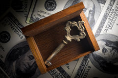 Old key and wooden chest on money. Royalty Free Stock Photo