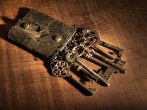 Old keyring and keys. An old leather keyring over a wooden table Royalty Free Stock Image