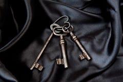 Old keys. Three old keys on a black silk Royalty Free Stock Photo