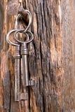 Old keys. Hanging two old keys on wooden background Stock Images