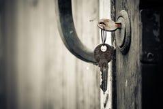 Old keys. Rusty keys in lock of vintage door Stock Images