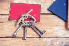 Old keys and documents. On wooden background stock images