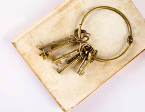 Old keys on old book Stock Photos