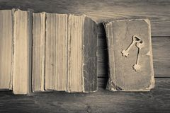 Old keys on a old book and stack of antique books on wooden back Stock Image