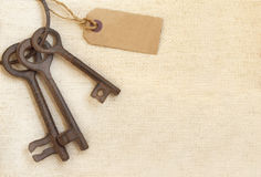 Old keys and paper label on canvas texture. Retro background with old keys and paper label on canvas texture Stock Photos