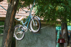 Old kid`s bicycle hang on rope Royalty Free Stock Photo