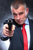 Old killer in suit and tie pointing his gun. Serious old killer in suit and tie pointing his gun to the camera Royalty Free Stock Photography