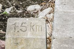 Old Kilometer stone says ` 1.5 KM.` to get into the destination. stock images