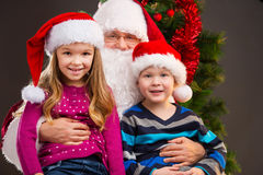 Old kind Santa Claus holding two little kids on his knees. royalty free stock images
