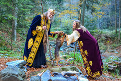 The old king, a queen and a small hunting dog Stock Photos