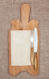 Old kitchen board with aged paper, fork and knife Royalty Free Stock Image