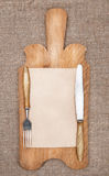 Old kitchen board with aged paper, fork and knife Royalty Free Stock Images