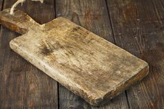 Old kitchen board on a black wooden table. Cutting board stock photo
